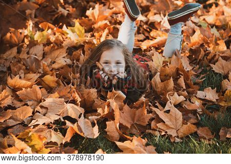 Cute Little Girl In Autumn Park. Little Girl In Leaves. Happy Child Laughing And Playing Leaves In A