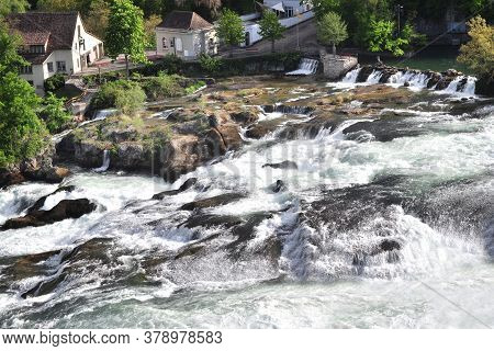 Rapid Stream Among The Rocky Banks Of The Rhine Falls In Switzerland