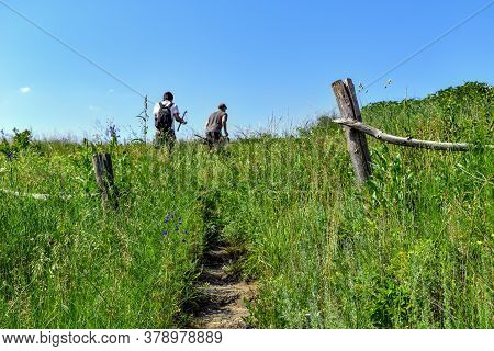Dirt Path With Steps On A Hill Among Lush Green Grass And Two Male Blurred Silhouettes At The Top. T