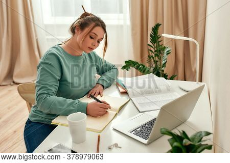 Distance Education. Young Beautiful Woman, Student In Casual Clothes Sitting At Office Desk And Writ