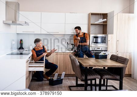 Full Length Shot Of Two Handymen, Workers In Uniform Talking While Assembling Kitchen Cabinet Using