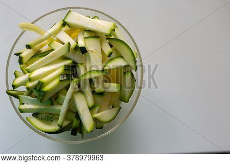 Sliced Zucchini Slices In A Transparent Plate On A White Background.