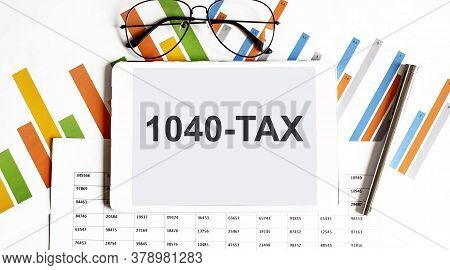 The Tablet With Text 1040-tax On Business Charts And Pen