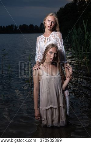 Two Young Twin Sisters With Long Blond Hair Posing In Light Dresses In Water Of Lake At Summer Night