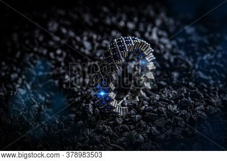Silver Ring With Blue Stones On Black Coal Background