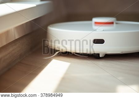 A White Robot Vacuum Cleaner Vacuums Along The Skirting Board Near A Large Window Through Which The