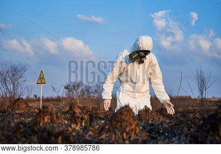 Environmentalist In Gas Mask And Protective Suit Staring At Burnt Field In Despair. Male Ecologist L