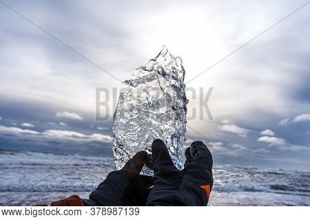 Male Hand In A Winter Glove Holds A Piece Of Glacier In Iceland.