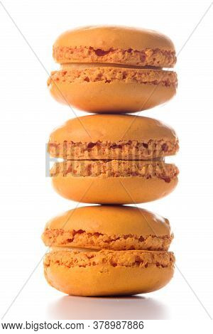 Three Orange Flavoured Macaroons Standing On Top Of Each Other On White Background.