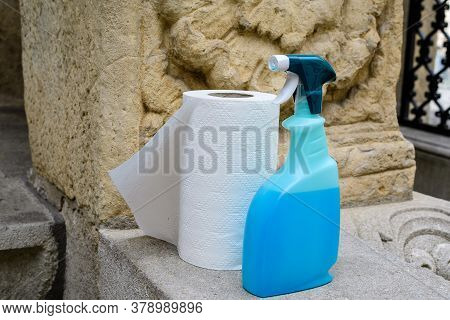 One Kitchen Napkins Paper Role And One  Botle With Disinfectant Soap Are Displayed In Front Of A Sto