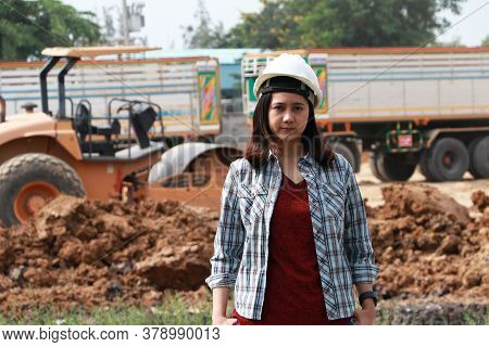 Female Civil Engineer With White Helmet, Standing With Loader Pedal Car And Pile Of Soil Background