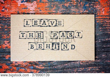 Cardboard With Words Leave The Past Behind Made By Black Alphabet Stamps On Wooden Background.