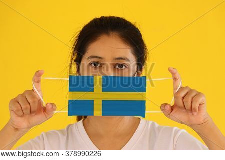 A Woman In White Shirt With Sweden Flag On Hygienic Mask In Her Hand And Lifted Up The Front Face On