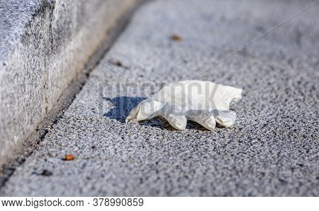 Close-up Image Of A Surgical Glove Dropped And Abandoned In The Streetduring The Coronavirus Crisis