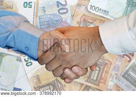 Handshake Of Two Hands Men Closeup On Background Euro Banknotes. Handshake Over Euro Money. Image Of