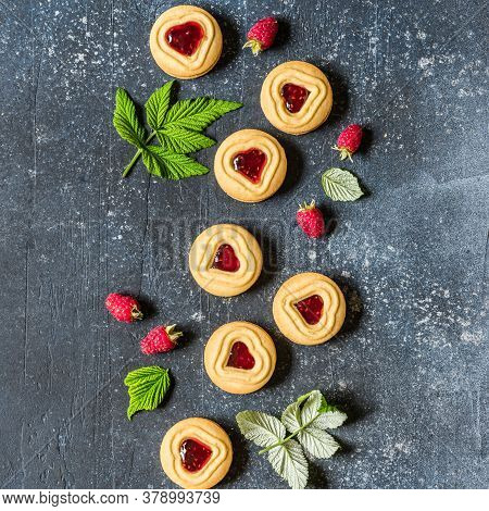 Shortbread Butter Cookies With Raspberry Jam Filling Center, Fresh Berries And Leaves, Blue Concrete