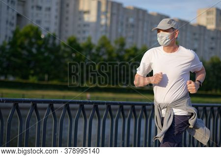 Mature Caucasian man in medical face mask jogging in the city