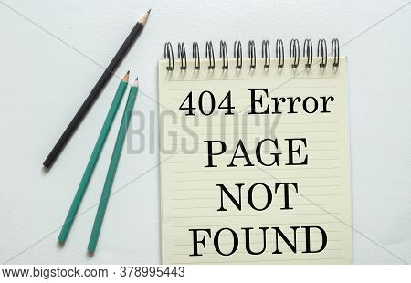 Two Green One Black Pencil With Text 404 Error Page Not Found In The Notebook On The White Backgroun