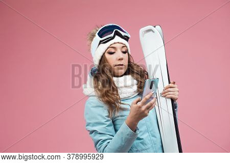 Young Woman With Skis Uses A Smartphone To Plan Her Ski Runs. Winter Holidays At A Ski Resort. Girl