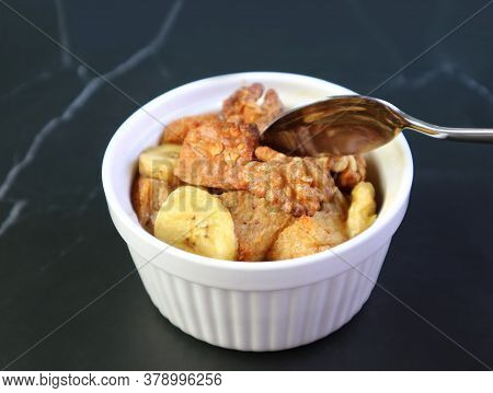 Closeup Mouthwatering Banana Walnut Bread Pudding In A Ceramic Bowl Isolated On Black Table