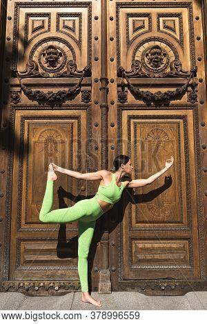 Spanish Woman Doing Yoga Over Big Wood Door . Yoga Concept.