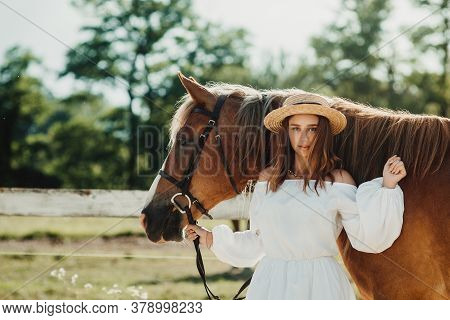 Beautiful Hippie Girl With Horse On A Ranch Background, Front View. The Girl In The Hat.
