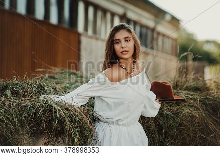 Beautiful Hippie Girl On A Ranch Background, Front View. The Girl In The Hat.