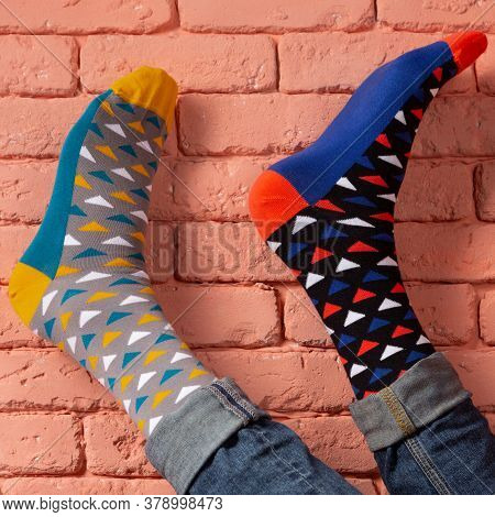 Two Male Legs In Socks Of Different Color, Close-up, On A Brick Wall Background