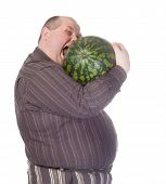 Obese man with a huge belly attempting to bite into a watermelon as his insatiable appetite gets the better of him before he can cut it humorous spoof on white poster