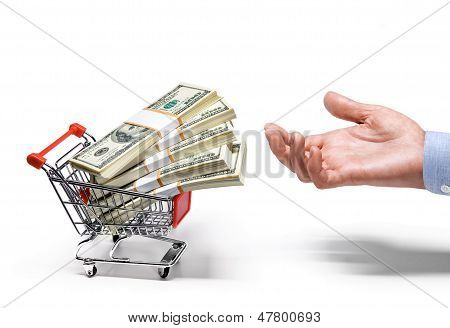 businessman's hand & shopping cart full of stacks of american dollar banknote - isolated on white b