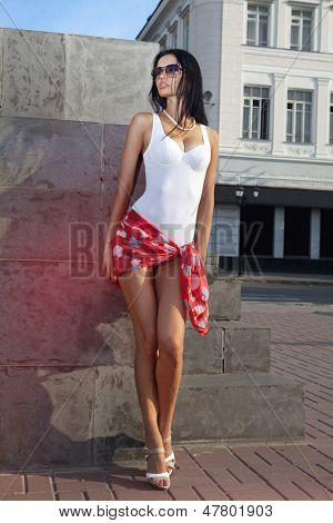leggy beautiful lady standing on sidewalk of city