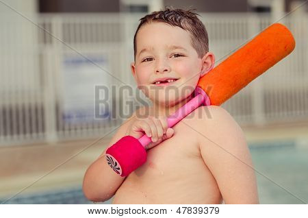 Happy child with his water toy at pool during summer