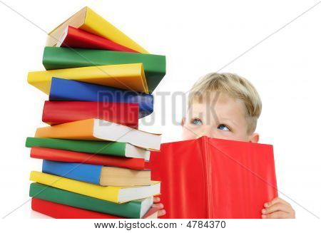 Five year old boy reading a book with a stack of books next to him. Isolated on white. poster