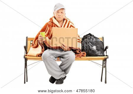 Homeless mature man sitting on a bench, his worldly possessions next to him, holding a blank cardboard isolated on white background  poster