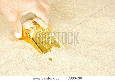 Digging up a gold bar in sand