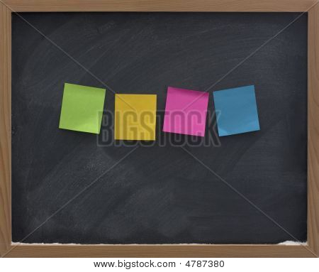 four blank colorful (green yellow red blue) sticky notes on blackboard with strong eraser smudge patterns poster