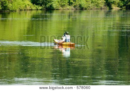 A Man Kayaking On A Lake