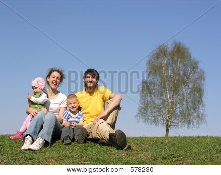 Sitting Family With Two Children. Spring.