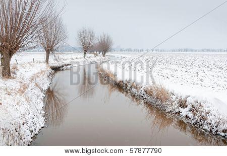 Meandering Ditch In A Rural Landscape Covered With Snow