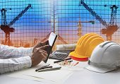 hand of architect working on table with tablet computer and working tool equipment against reflection of office building and crane construction use for civil engineering and construction industry business poster