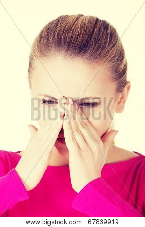 Young caucassian woman is having sinus pressure, touching her nose. Isolated on white.