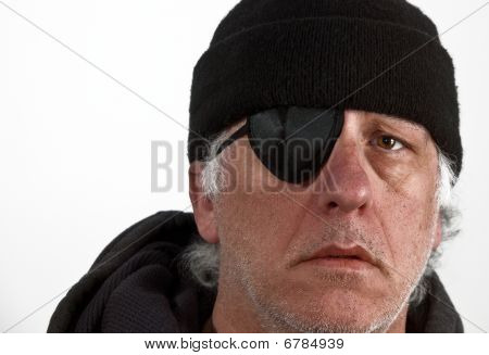 Older gray haired man with eye patch and scally cap