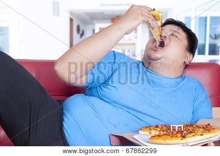 Obese Person Bite A Slice Of Pizza