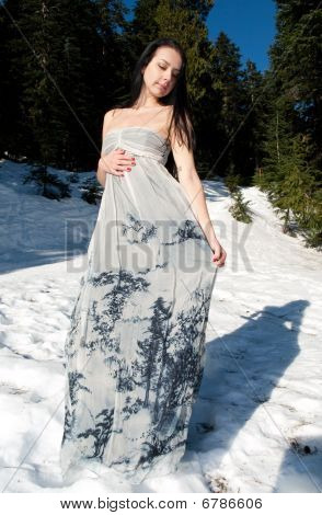 Beautiful woman with airy dress posing in the snow