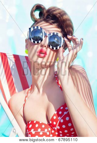 Colorful summer portrait of young attractive woman wearing bikini and sunglasses sitting by the swimming pool