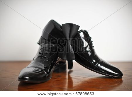 Groom shoes. Stylish black wedding shoes. Black man leather shoe with shoelace on wooden floor