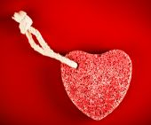 heart-shaped stone with rope on red background poster