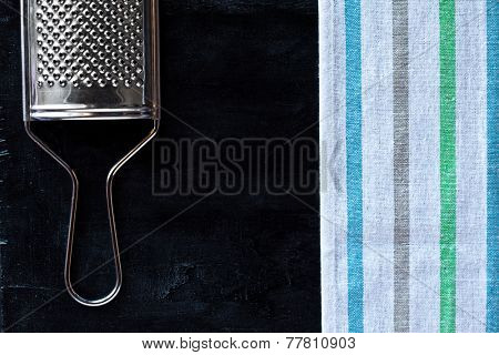 metal grater and tablecloth over blackboard background