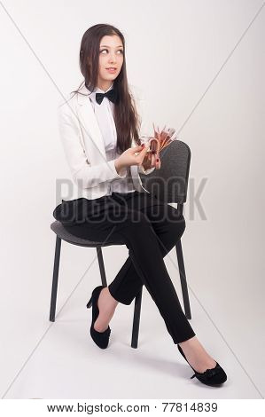 Attractive businesswoman with cash sits on chair