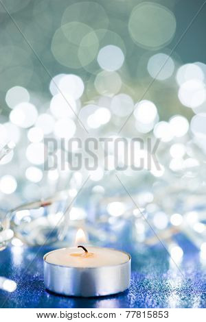 Candle with flame on sparkles background